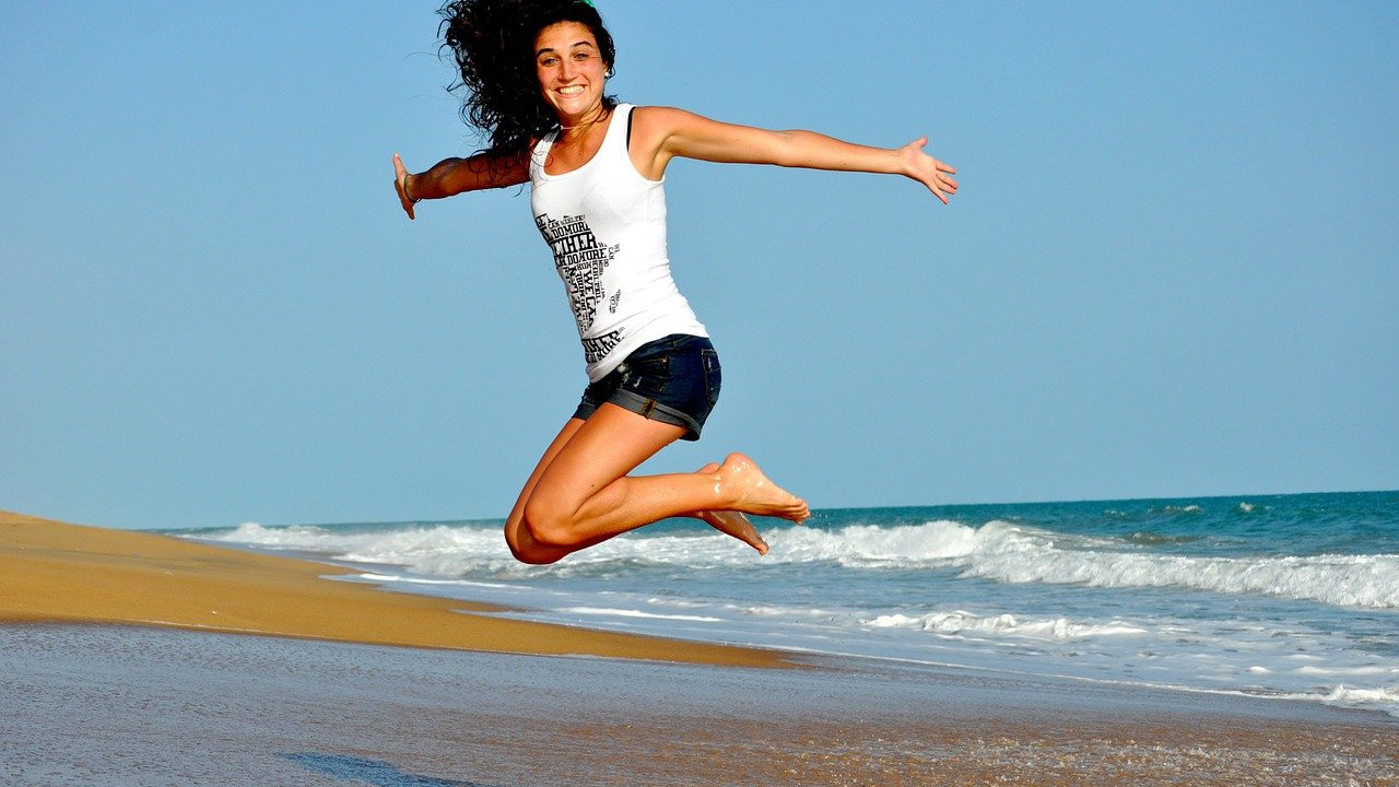 young brunette woman jumping at the beach